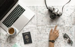 a persons hand in front of the pc, passport and camera